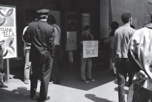 Il gruppo Occupy Museums effettua la sua prima azione pubblica di protesta di fronte al MoMA, 2011 (la maschera a forma di moneta è indossata dallo scultore Noah Fischer), foto: Jerry Saltz